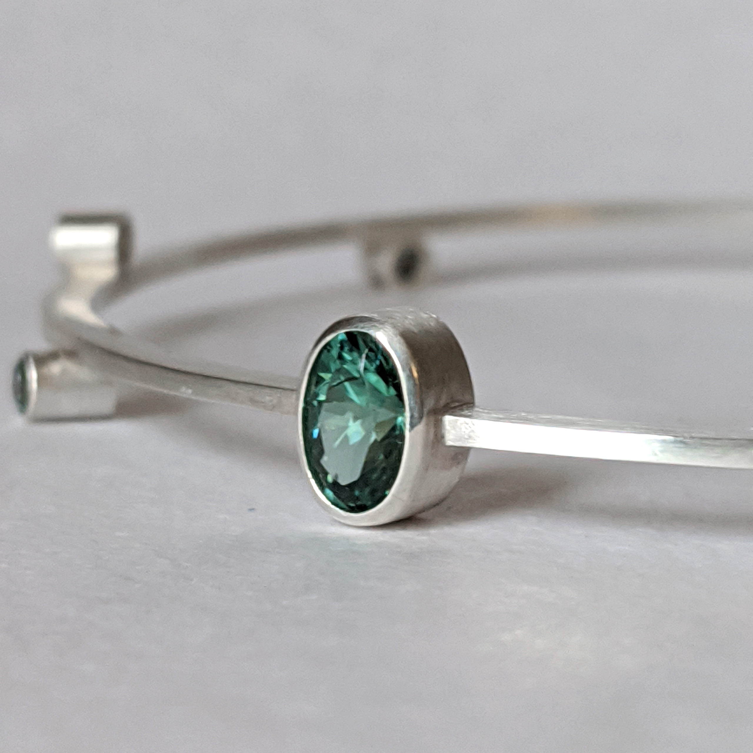 Oval Bangle Bracelet in Silver with Blue-Green Indicolite Tourmaline and Green Sapphires